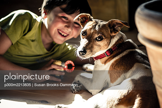 Germany, Boy playing with dog - p300m2213835 by Susan Brooks-Dammann