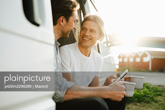 Smiling gay couple with coffee cup spending leisure time in camping van on sunny day - p426m2296289 by Maskot