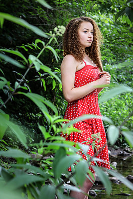 Female teenager with curly head and red dress - p1019m1462251 by Stephen Carroll