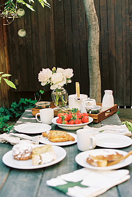Breakfast table with tea, pastries and fresh strawberries. - p1100m1080255 by Mint Images