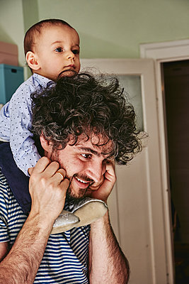 Father gives baby boy a piggyback ride, Stay at home due to Covid-19 - p1146m2182018 by Stephanie Uhlenbrock