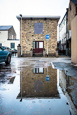 The end of a modern stone building reflected in a puddle on the road - p1302m1223563 by Richard Nixon