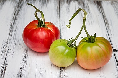 Oxheart tomatoes on wooden board - p300m838634f by Susan Brooks-Dammann