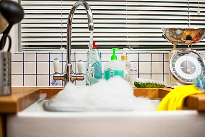 Water from kitchen faucet left running into sink - p429m1012876f by Seb Oliver