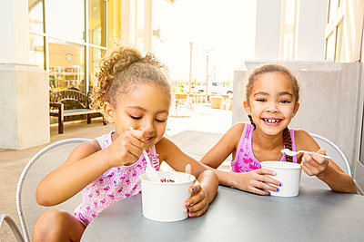Mixed race sisters eating ice cream at outdoor cafe - p555m1413904 by Inti St Clair