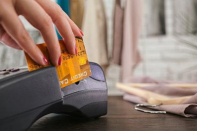 Woman swiping credit card through credit card reader - p555m1420789 by Lumina Images