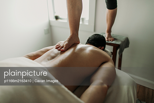 Massage therapist uses her feet to treat male patient\'s back
