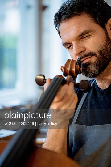 Handwerker - Arbeit an dem Cello in der Werkstatt - p1212m1203416 von harry + lidy