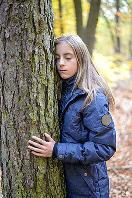 Portrait of girl with eyes closed touching tree in the woods - p300m2078908 by Bernd Friedel