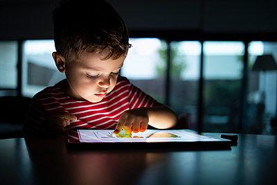 Boy using digital tablet at home - p300m2252592 by Ignacio Ferrándiz Roig