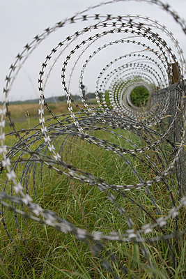 Germany, Bavaria, Oberpfaffenhofen, Barbed wire fence at airport - p300m940888f by Claudia Rehm