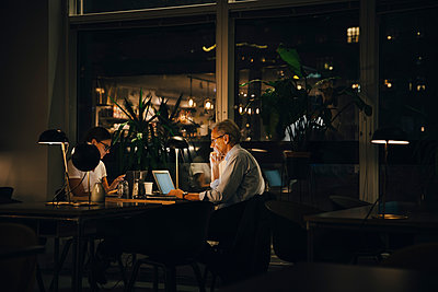 Male and female professionals working late in dark office at night - p426m2194735 by Maskot