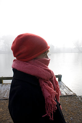 Woman wrapped up in winter by a lake - p1121m1111513 by Gail Symes
