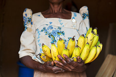 Africa, Uganda, African woman with fresh bananas - p1167m2283489 by Maria Schiffer