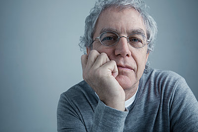 Portrait serious Caucasian senior man with gray hair and eyeglasses leaning with hand on chin - p1192m1213223 by Hero Images