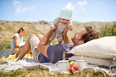 Junge Familie macht ein Picknick - p1355m1574059 von Tomasrodriguez