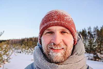 Mid adult man face covered in snow during winter - p300m2265142 by Ekaterina Yakunina