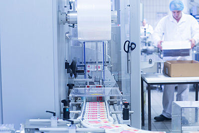 Workers packaging pharmaceutical products on production line in pharmaceutical plant - p429m1418435 by Sigrid Gombert