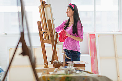 Mixed race teenage girl painting in studio - p555m1415304 by JGI/Tom Grill