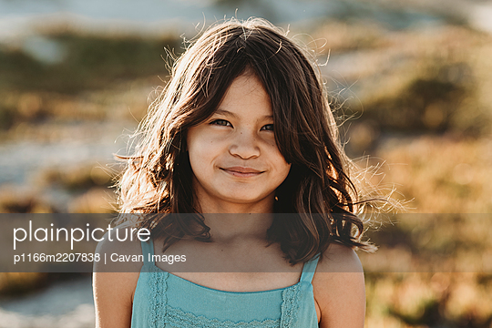 Young girl with brown eyes and thick dark hair wearing blue tank top - p1166m2207838 by Cavan Images
