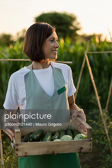 Woman with wooden box in garden - p300m2121440 von Mauro Grigollo