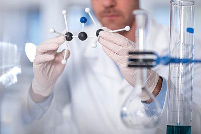 Scientist working in lab holding molecular structure - p300m1499425 by zerocreatives