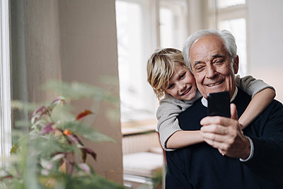 Happy grandfather and grandson using cell phone at home - p300m2120381 by Gustafsson