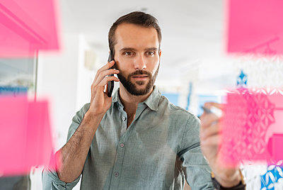 Young businessman talking on mobile phone about adhesive note at office - p300m2265042 by Daniel Ingold