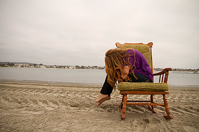 Woman sitting in armchair on beach - p555m1409336 by Shestock