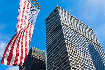 Low angled view of skyscrapers and American flag in financial district, Manhattan, New York, USA - p924m973926f by Ditto