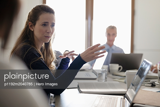 Female doctor talking with colleagues in conference room meeting - p1192m2040785 by Hero Images