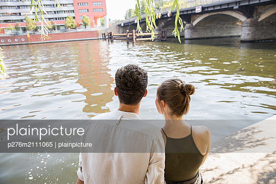 Young couple is resting by the water - p276m2111065 by plainpicture