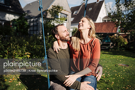 Affectionate couple sitting on swing in in their garden - p300m2166739 by Kniel Synnatzschke