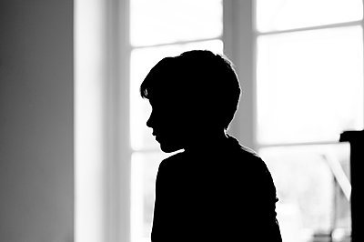 Little boy sitting quietly in silhouette - p1228m2260787 by Benjamin Harte