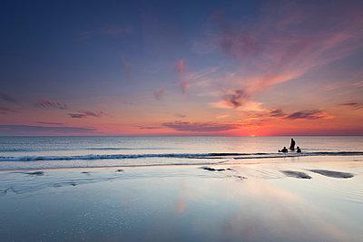 Denmark, Romo, Lakolk, silhouettes of three bathing people enjoying sunset - p300m1029040f by Marco Rank