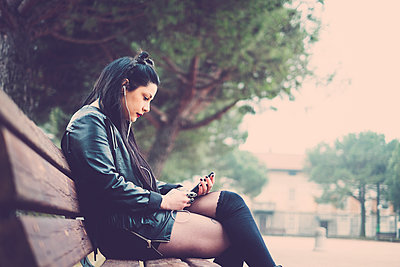 Dark-haired young woman sitting on bench listening music with earphones and smartphone - p300m1356278 by Simona Pillola