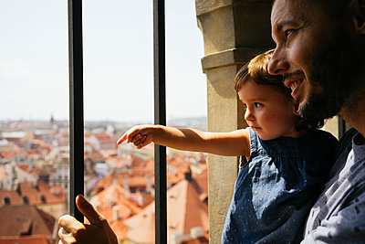Czechia, Prague, father and little daughter looking together at view from the old town hall - p300m2029263 von Gemma Ferrando