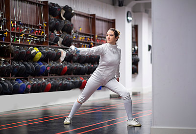 Woman in fencing outfit practicing at gym - p300m2243589 by Jose Carlos Ichiro