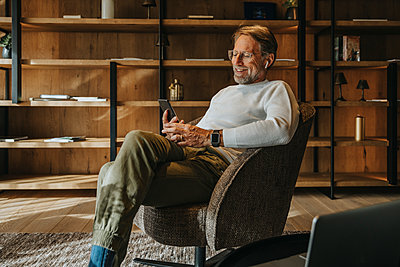 Smiling mature man using mobile phone while sitting on armchair - p300m2266742 by Mareen Fischinger