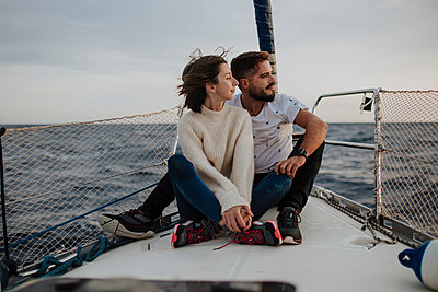 Girlfriend and boyfriend sitting on sailboat during vacation - p300m2274875 by Gala Martínez López