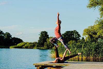 Women practicing acroyoga on sunny lakeside dock - p301m2075572 by Sven Hagolani