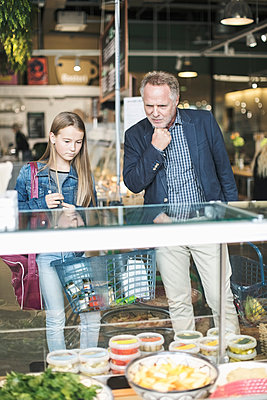 Father and daughter looking in display cabinet while shopping at supermarket - p426m1407388 by Kentaroo Tryman