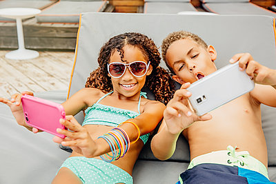 Mixed race children taking selfie with cell phones on patio - p555m1408570 by Inti St Clair