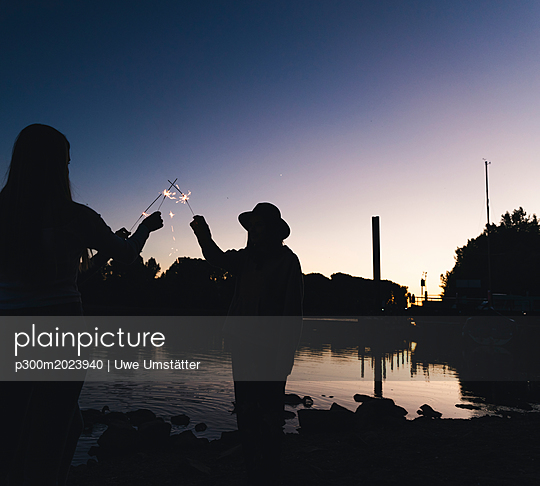 Silhouette of people at the riverside holding sparklers in the evening - p300m2023940 von Uwe Umstätter