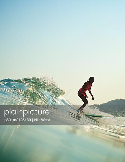 Female surfer riding ocean wave - p301m2123139 by Nik West