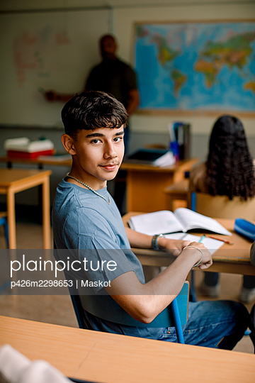 Portrait of teenage boy in high school classroom - p426m2298653 by Maskot