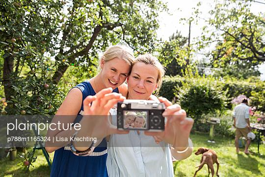 Freundinnen machen ein Selfie im Garten - p788m1165324 von Lisa Krechting