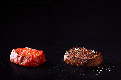 Gegrilltes Rindersteak und rohes Rindersteak isoliert auf schwarzem Hintergrund - p1053m2168303 von Joern Rynio