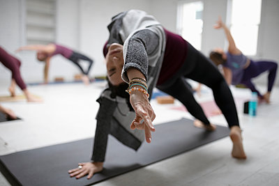 Woman practicing yoga backbend pose and gyan mudra in yoga class - p1192m1583332 by Hero Images