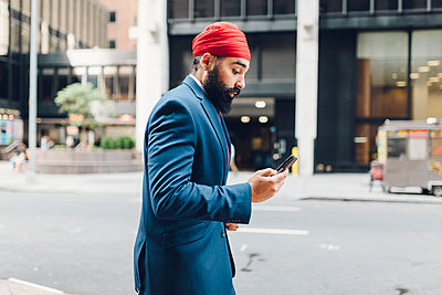 Indian businessman in Manhattan using smartphone, walking in the street - p300m1189641 by Giorgio Fochesato